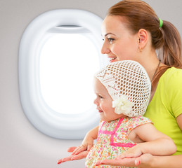 Happy mother and child sitting together in airplane cabin near w