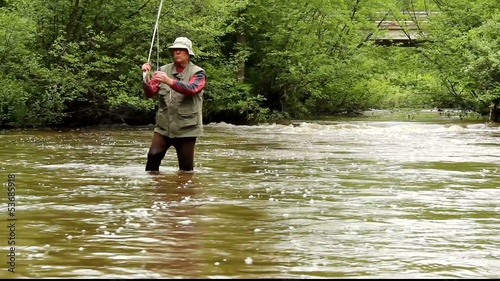 fisherman walking upstream in a river