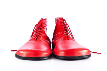 Very big red clown shoes on white