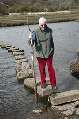 Man on stepping stones crossing river