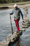 Man walking on stepping stones over river