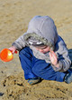 Cute child playing on the wet beach sand