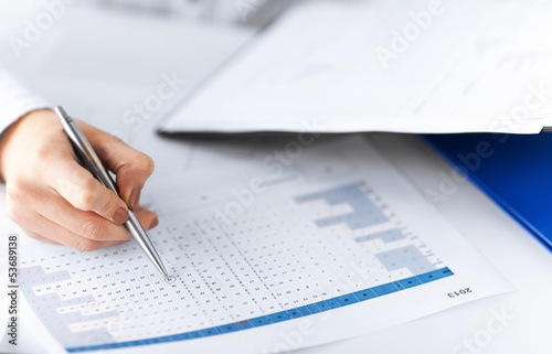 woman hand wrtiting on paper with numbers