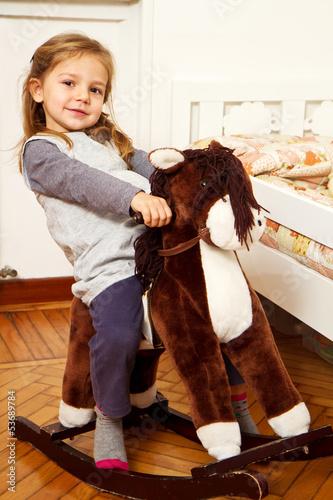 bambina su cavallo a dondolo