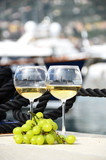 Pair of wineglasses and grapes against the yacht pier of La Spez