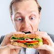 Comical man eating sandwich with funny expression