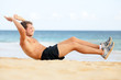 Fitness man doing crunches sit-ups on beach