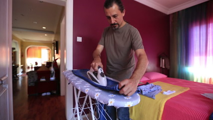 man ironing a jean at home