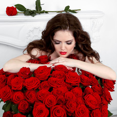 Young beautiful woman leaning on the red roses bouquet. Valentin