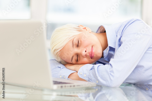 Exhausted businesswoman sleeps on notebook