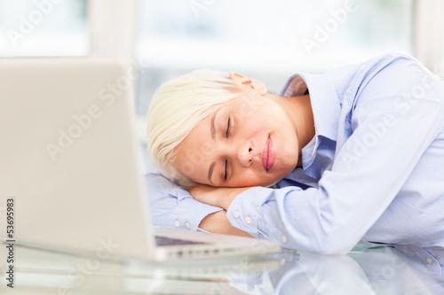 Exhausted businesswoman sleeps on notebook