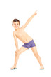 Full length portrait of a boy in swimming shorts gesturing with