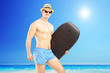 Male surfer holding a surfboard and looking at camera on a sunny
