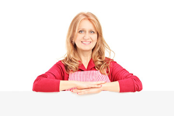 Mature smiling female wearing an apron and posing on a blank pan