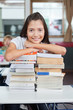Schoolgirl Leaning On Stacked Books At Desk
