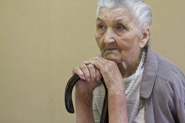 sad old lady contemplating with walking stick