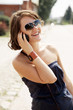 girl is speaking by phone and laughs with sun glasses and bangle