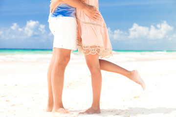 legs of young kissing couple on tropical turquoise boracay beach