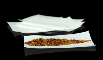 Tobacco and rolling papers, isolated on black