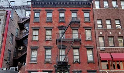 Façade en briques rouges avec escalier de secours.