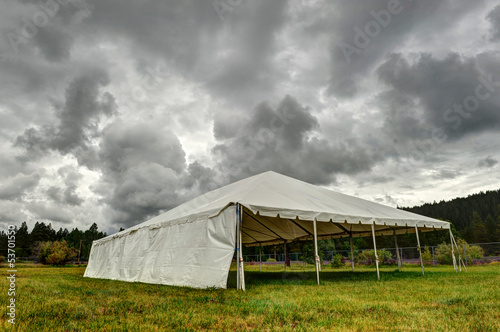 White tent under dark clouds in a field