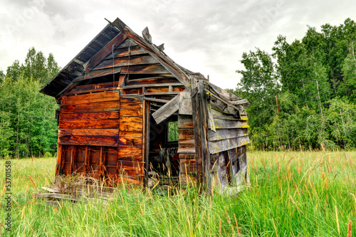 Abandoned wooden shed in a grass field