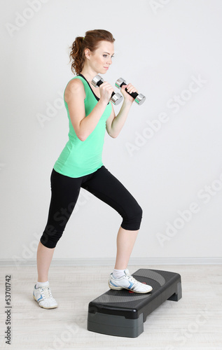 Beautiful young woman exercises with dumbbell on stepper