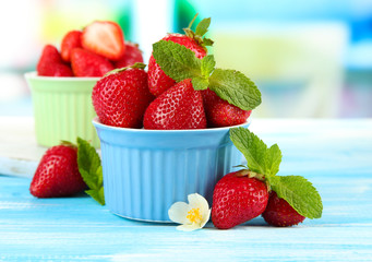 Ripe sweet strawberries in bowls on blue wooden table