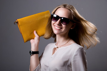 Portrait of cheerful beautiful girl in sunglasses holding a clut