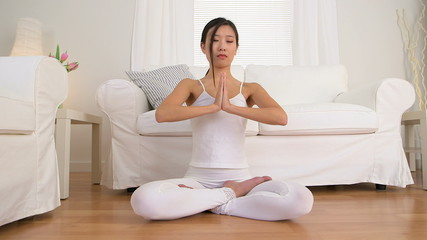 Chinese woman meditating in living room
