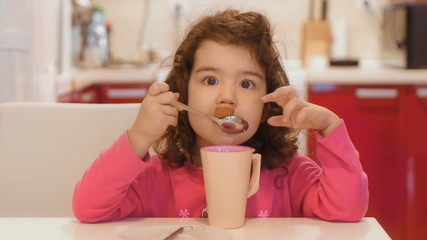 Little girl trying to eat with a spoon
