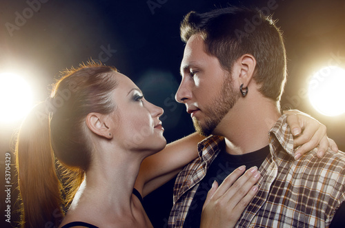 Beautiful young couple in love. The girl embraces the guy's neck