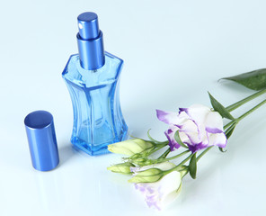 Perfume in bottle and flowers isolated on white