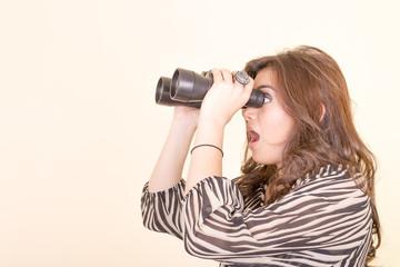 cute woman holding binoculars, yellow background