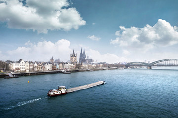 Cologne cityline with cargo ship on rhine