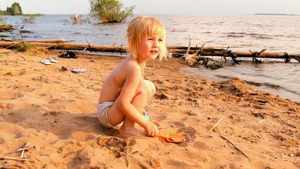 маленькая девочка играет в песке на берегу водоёма