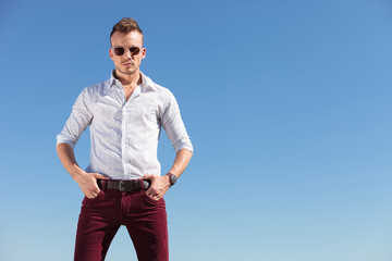 casual man with hands in pocket in front of blue sky