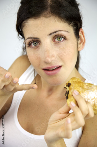 Smiling woman with sweet snack in her hand
