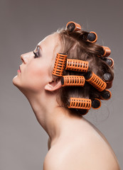 Stylish girl portrait with fashion makeup and hair curlers, isol