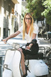 Young businesswoman sitting on a italian scooter.