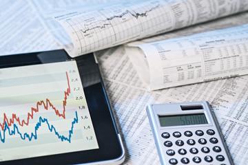 Aktienkurse auf dem Tablet und in der Zeitung