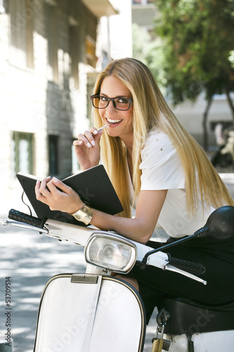 Young businesswoman writing a notebook on a italian scooter.