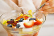 Closeup on fruits salad in hand of woman