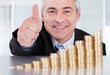 Businessman With Coins Showing Thumbs Up Sign