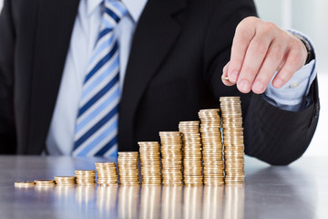 Close-up Of Businessman Hand Put Coins To Stack Of Coins