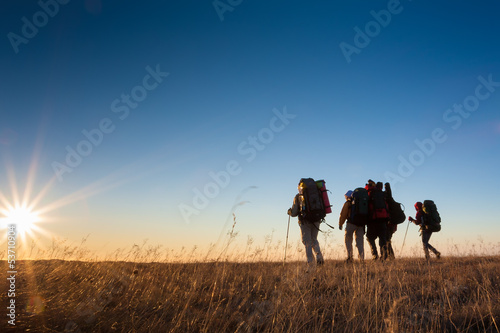 Hikers is walking on plateau in Crimea mountains during sunset