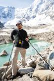 Hiker is standing at glacier lake in Caucasus mountains in Bezen