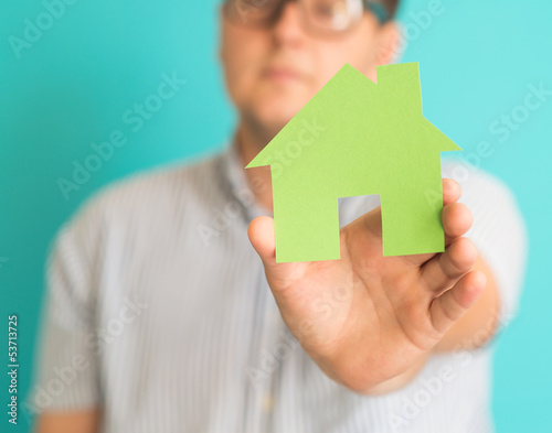 young man holding a small house