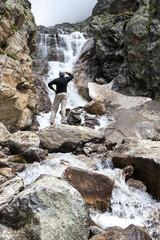 Hiker is standing near waterfall in Caucasus mountains in Bezeng