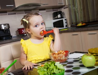 Little girl who eat healthy food in the kitchen